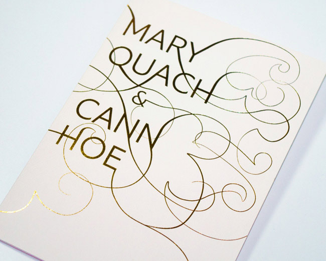 The cover of a stunning gold foil swirl invitation printed on felt paper.